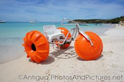 Giant tricycle with orange wheels at Dickenson Beach in Antigua.jpg