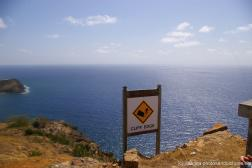 Cliff edge sign and view of the Caribbean ocean in Antigua as viewed from Shirley Heights.jpg