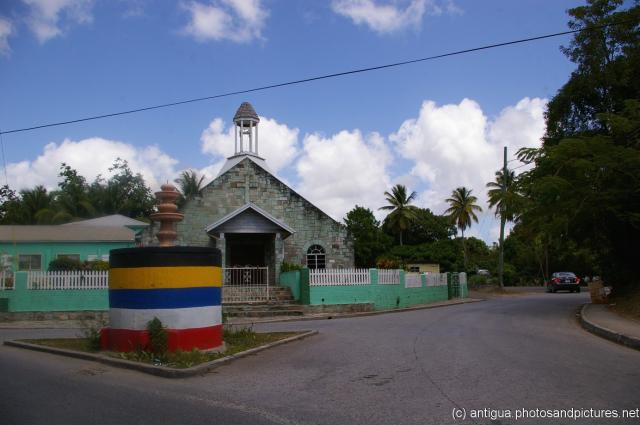Fountain atop a color striped column and a church at the fork of a road in Antigua.jpg