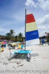 Mini catamaran with colorful sail at Dickenson Beach Antigua.jpg
